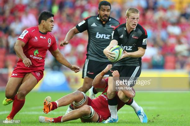 Johnny McNicholl of the Crusaders is tackled by Jake Schatz of the Reds during the round 13 Super Rugby match between the Reds and the Crusaders at...