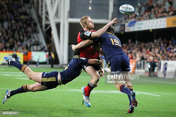 Johnny McNicholl of the Crusaders makes a pass as he is tackled during the round 15 Super Rugby match between the Highlanders and the Crusaders at...