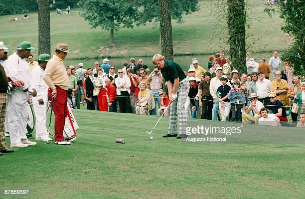 Johnny Miller tees off as Sam Snead and Billy Casper watch during the 1975 Masters Tournament at Augusta National Golf Club in April 1975 in Augusta...