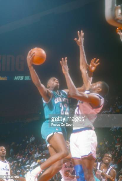 Johnny Newman 22 of the Charlotte Hornets looks to get his shot off over Charles Jones of the Washington Bullets during an NBA basketball game circa...