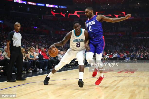 Johnny O'Bryant of the Charlotte Hornets is defended by Sindarius Thornwell of the LA Clippers at Staples Center on December 31 2017 in Los Angeles...