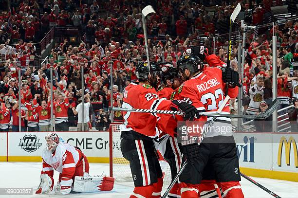 Johnny Oduya and Michal Rozsival of the Chicago Blackhawks hug teammate Patrick Kane after Kane scored in the first period as goalie Jimmy Howard of...