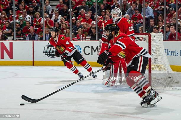 Johnny Oduya of the Chicago Blackhawks approaches the puck next to teammate goalie Corey Crawford as Niklas Hjalmarsson of the Blackhawks skates in...