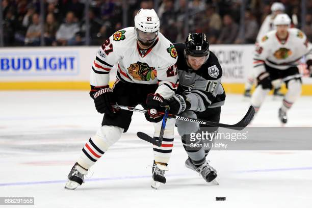 Johnny Oduya of the Chicago Blackhawks battles Kyle Clifford of the Los Angeles Kings for a loose puck during the second period of a game at Staples...