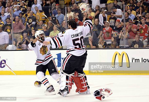 Johnny Oduya of the Chicago Blackhawks celebrates with Corey Crawford after defeating the Boston Bruins in Game Six of the 2013 NHL Stanley Cup Final...