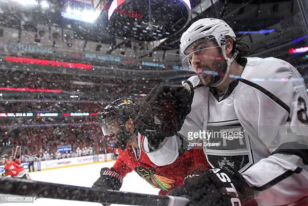 Johnny Oduya of the Chicago Blackhawks checks Drew Doughty of the Los Angeles Kings near the side boards in the first period of Game Two of the...