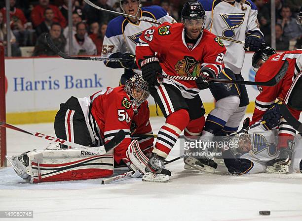 Johnny Oduya of the Chicago Blackhawks clears the puck away from Corey Crawford as TJ Oshie of the St Louis Blues hits the ice in front at the United...