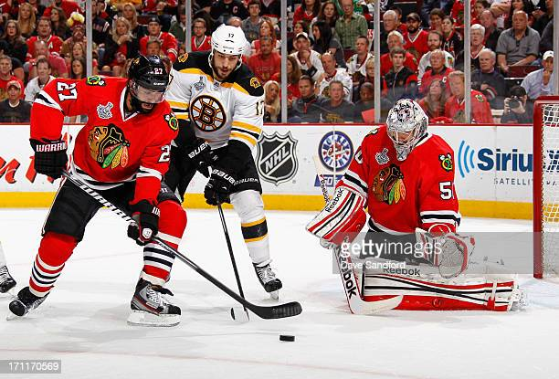 Johnny Oduya of the Chicago Blackhawks clears the puck in fron of teamate Corey Crawford and Milan Lucic of the Boston Bruins during the first period...