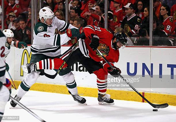 Johnny Oduya of the Chicago Blackhawks controls the puck as he is shoved by Charlie Coyle of the Minnesota Wild in Game One of the Western Conference...