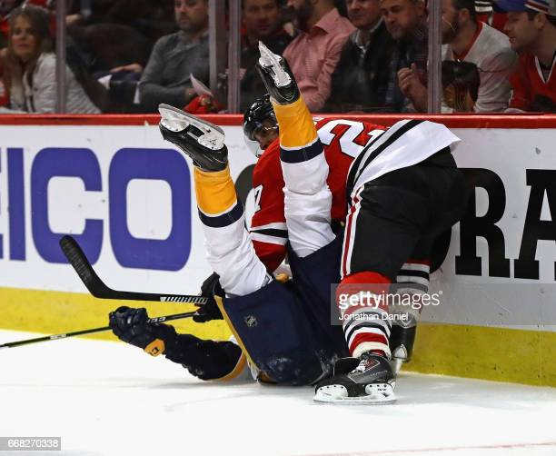 Johnny Oduya of the Chicago Blackhawks dumps Filip Forsberg of the Nashville Predators behind the net in Game One of the Western Conference First...