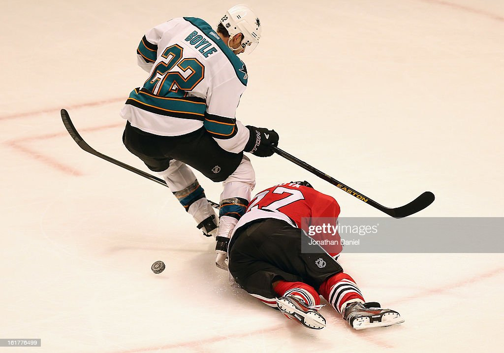 Johnny Oduya #27 of the Chicago Blackhawks falls and collides with Dan Boyle #22 of the San Jose Sharks at the United Center on February 15, 2013 in Chicago, Illinois. The Blackhawks defeated the Sharks 4-1.