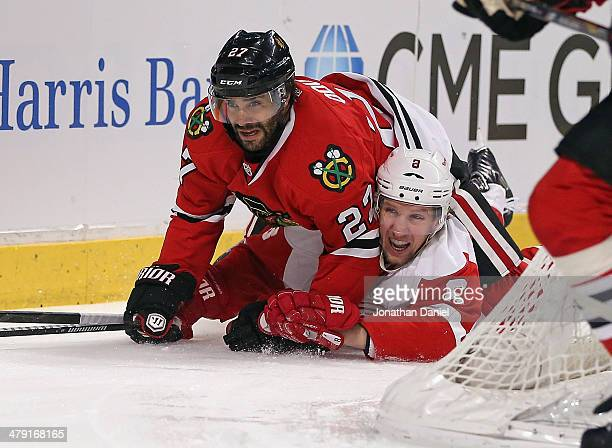 Johnny Oduya of the Chicago Blackhawks lands on top of Justin Abdelkader of the Detroit Red Wings at the United Center on March 16 2014 in Chicago...