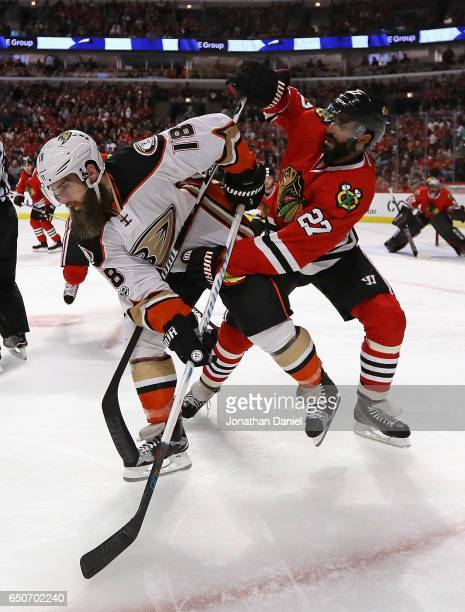 Johnny Oduya of the Chicago Blackhawks tangles with Patrick Eaves of the Anaheim Ducks at the United Center on March 9 2017 in Chicago Illinois
