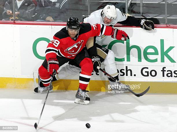 Johnny Oduya of the New Jersey Devils and Evgeni Malkin of the Pittsburgh Penguins fight along the boards for position on a loose puck at the...