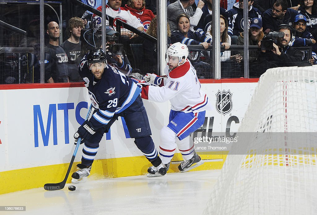 Johnny Oduya #29 of the Winnipeg Jets plays the puck along the boards as Louis Leblanc #71 of the Montreal Canadiens checks him from behind during first period action at the MTS Centre on December 22, 2011 in Winnipeg, Manitoba, Canada.