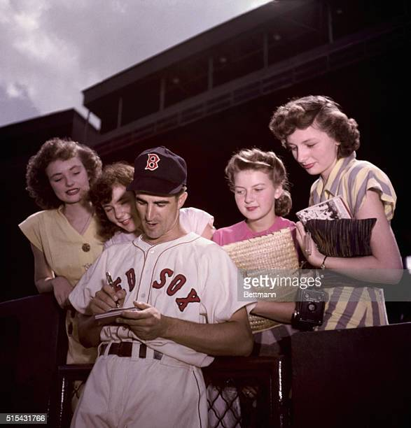 Johnny Pesky, Boston Red Sox baseball player, is shown signing autographs for girl fans.