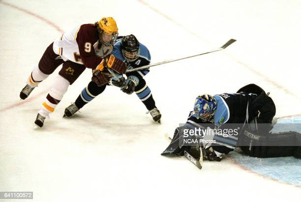 Johnny Pohl of Minnesota challanges Peter Metcalf and and Matt Yeats of the University of Maine during the Division 1 Men's Hockey Championship held...