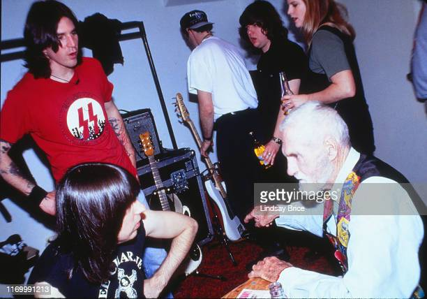 Johnny Ramone talks with Timothy Leary at the table as C.J. Ramones, standing, joins the conversation backstage before Ramones concert at the...
