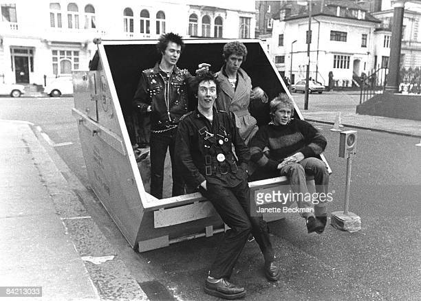 Johnny Rotten of the Sex Pistols makes faces while the group hangs about a trash bin London 1977 L to R Sid Vicious Johnny Rotten Steve Jones and...
