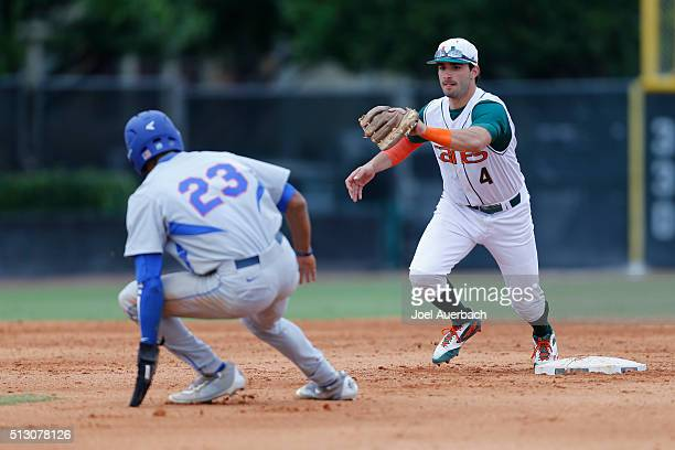 Johnny Ruiz of the Miami Hurricanes chases Buddy Reed of the Florida Gators as he is caught trying to steal second base on February 28 2016 at Alex...
