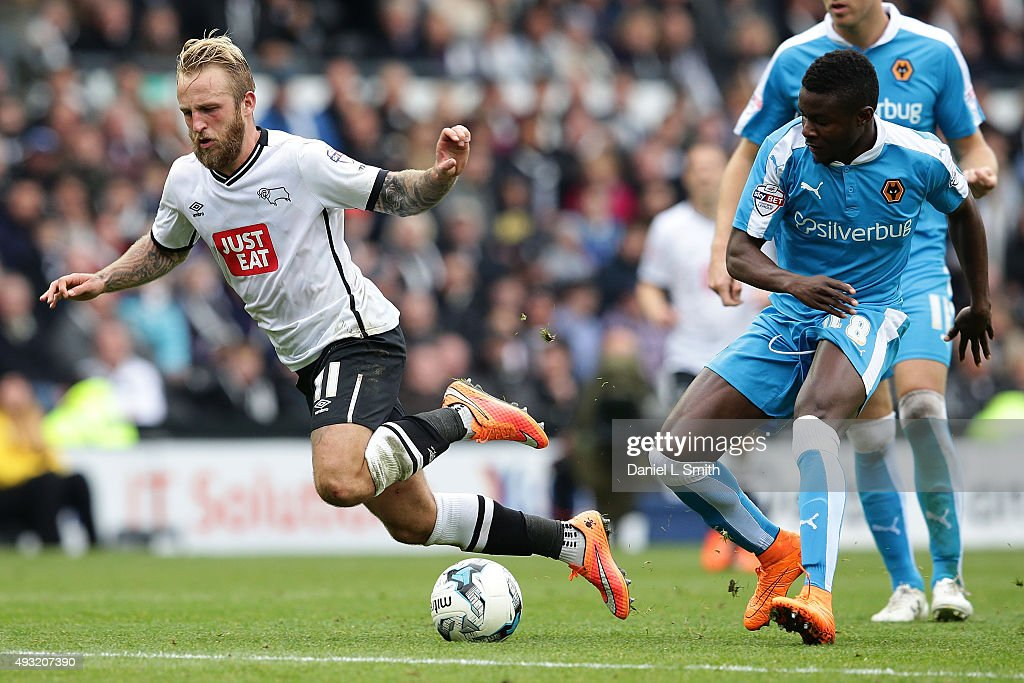 Johnny Russell of Derby County FC trips from a tackle from behind by Bright Enobakhare of Wolverhampton Wanderers FC during the Sky Bet Championship match between Derby County and Wolverhampton Wanderers at Pride Park Stadium on October 18, 2015 in Derby, England.