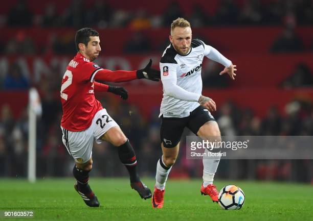 Johnny Russell of Derby County is chased by Henrikh Mkhitaryan of Manchester United during the Emirates FA Cup Third Round match between Manchester...