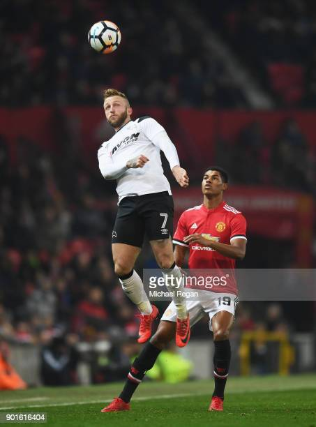 Johnny Russell of Derby County jumps ahead of Marcus Rashford of Manchester United during the Emirates FA Cup Third Round match between Manchester...
