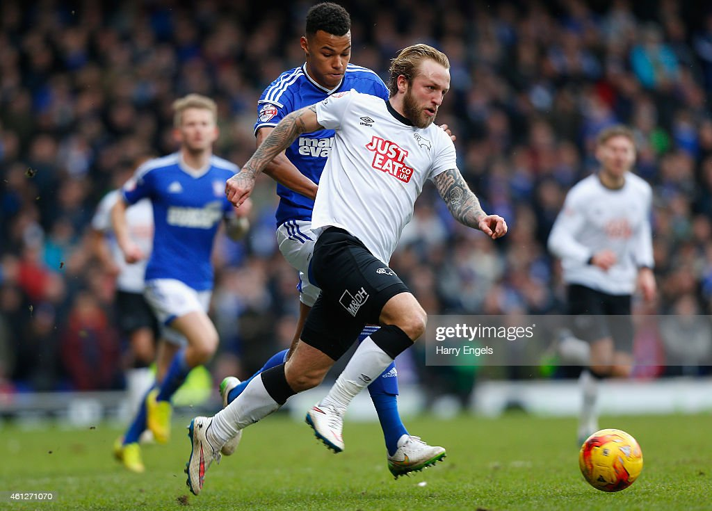 Johnny Russell of Derby County outpaces Tyrone Mings of Ipswich Town during the Sky Bet Championship match between Ipswich Town and Derby County at Portman Road on January 10, 2015 in Ipswich, England.