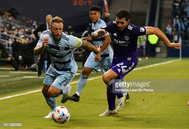 Johnny Russell of Sporting Kansas City attempts to get away from Kyle Smith of Orlando City SC during a game between Orlando City SC and Sporting...