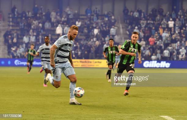 Johnny Russell of Sporting Kansas City dribbles toward the box as Zan Kolmanic of Austin FC tries to catch him during the gqme between Austin FC and...