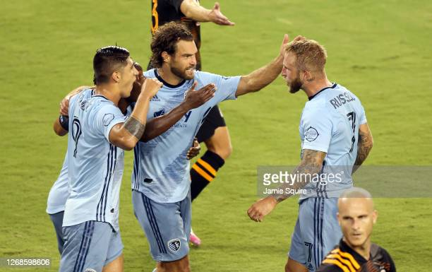 Johnny Russell of Sporting Kansas City is congratulated by Graham Zusi and Alan Pulido after scoring during the 1st half of the game against the...