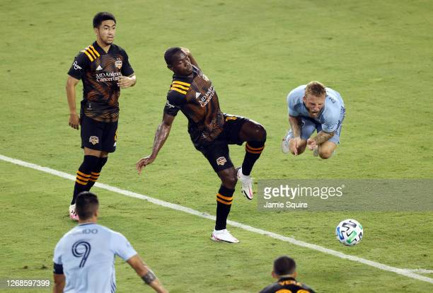 Johnny Russell of Sporting Kansas City is upended by Maynor Figueroa of Houston Dynamo during the game at Children's Mercy Park on August 25 2020 in...