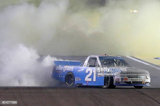 Johnny Sauter driver of the Allegiant Travel Chevrolet celebrates with a burnout after winning the NASCAR Camping World Truck Series Championship at...