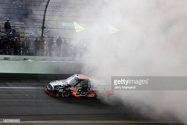 Johnny Sauter driver of the Carolina Nut Co/Curb Records Toyota performs a burnout to celebrate winning the NASCAR Camping World Truck Series NextEra...
