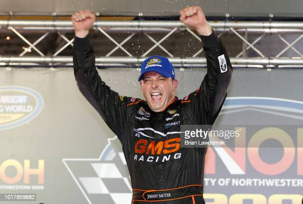 Johnny Sauter driver of the GMS Fabrication Chevrolet celebrates in Victory Lane after winning the NASCAR Camping World Truck Series UHOH 200 at...
