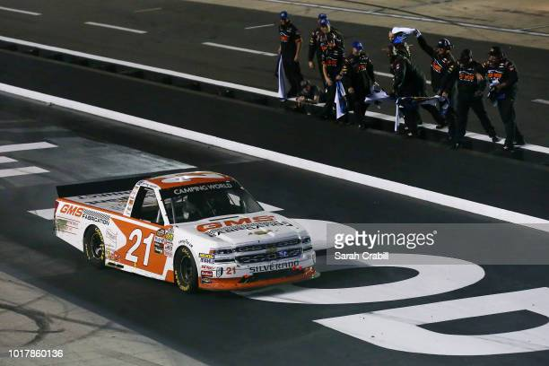 Johnny Sauter driver of the GMS Fabrication Chevrolet celebrates with his crew after winning the NASCAR Camping World Truck Series UHOH 200 at...