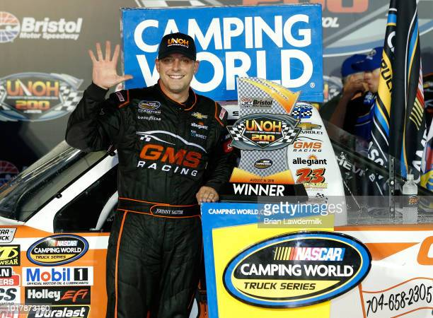 Johnny Sauter driver of the GMS Fabrication Chevrolet celebrates with the trophy in Victory Lane after winning the NASCAR Camping World Truck Series...