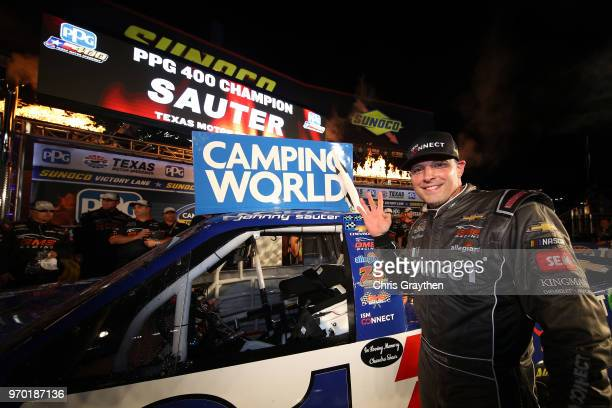 Johnny Sauter driver of the ISM Connect Chevrolet celebrates in Victory Lane by placing the winner's sticker on his car after winning the NASCAR...