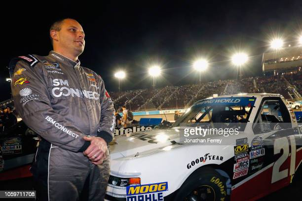 Johnny Sauter driver of the ISM Connect Chevrolet stands on the grid prior to the NASCAR Camping World Truck Series Lucas Oil 150 at ISM Raceway on...