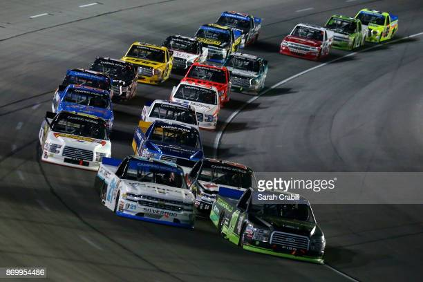 Johnny Sauter driver of the ISMConnect Chevrolet and Austin Cindric driver of the Fitzgerald Glider Kits Ford lead a pack of trucks during the NASCAR...