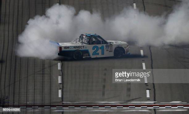 Johnny Sauter driver of the ISMConnect Chevrolet celebrates with a burnout after winning the NASCAR Camping World Truck Series JAG Metals 350 Driving...