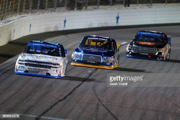 Johnny Sauter driver of the ISMConnect Chevrolet leads Chase Briscoe driver of the Cooper Standard Ford and Christopher Bell driver of the JBL Toyota...