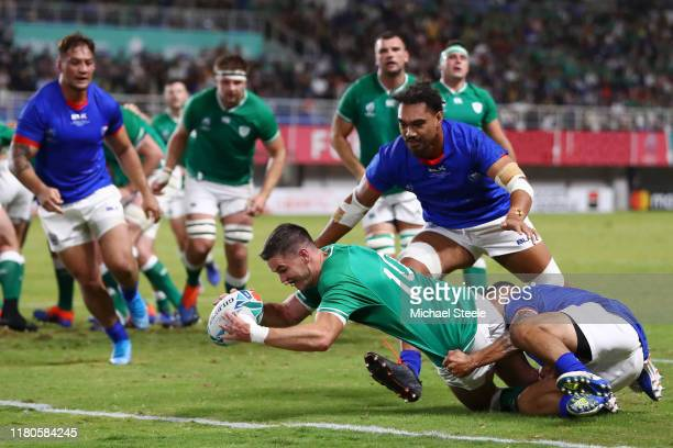 Johnny Sexton of Ireland scores his team's fourth try past Dwayne Polataivao and Chris Vui of Samoa during the Rugby World Cup 2019 Group A game...
