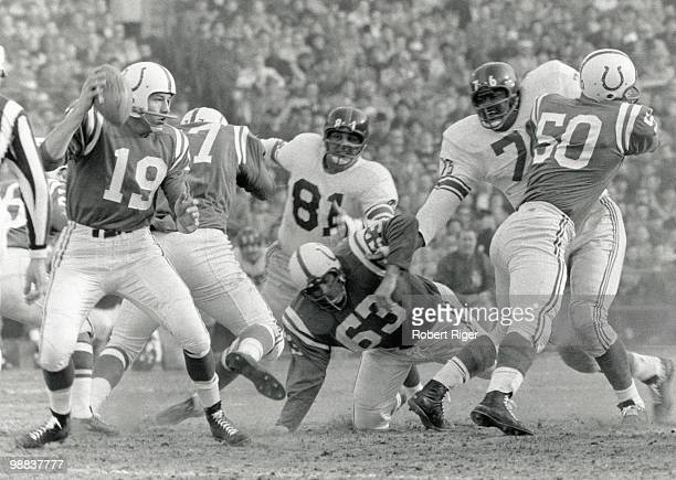 Johnny Unitas of the Baltimore Colts looks for a receiver as Art Spinney and Buzz Nutter block Andy Robustelli and Rosey Grier of the New York Giants...