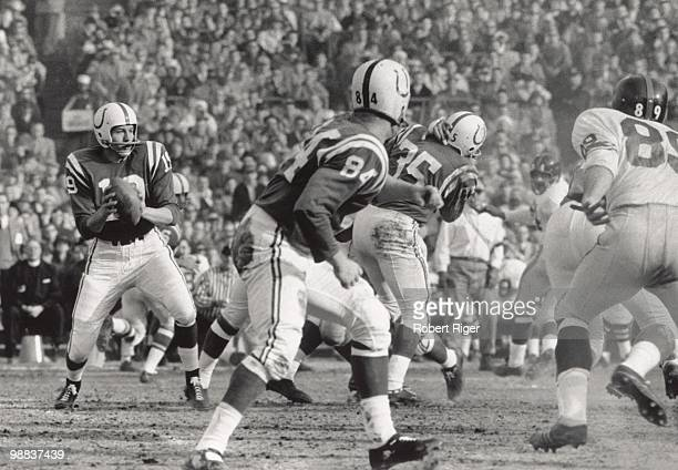 Johnny Unitas of the Baltimore Colts looks for a receiver as Jim Mutscheller watches the action against the New York Giants during the 1959 NFL...