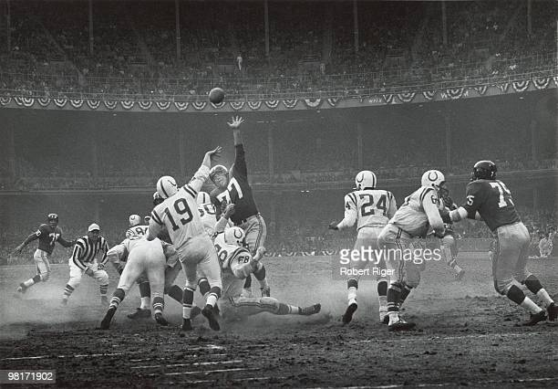 Johnny Unitas of the Baltimore Colts passes against Dick Modzelewski of the New York Giants during the 1958 NFL Championship game at Yankee Stadium...