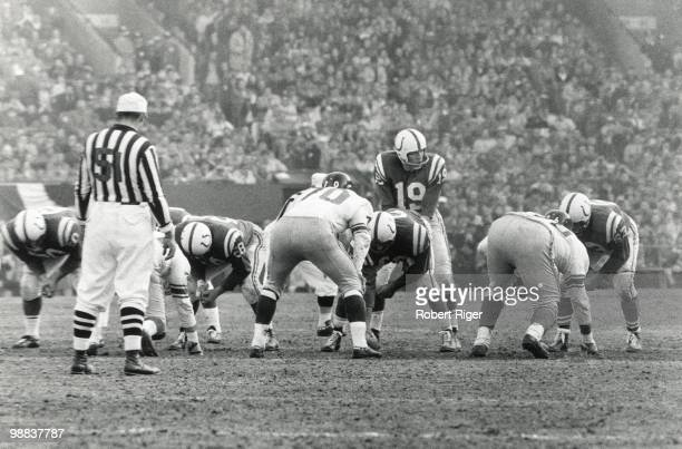 Johnny Unitas of the Baltimore Colts stands under center Buzz Nutter as Sam Huff of the New York Giants lines up to defend during the 1959 NFL...