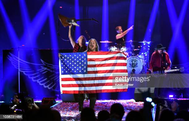 Johnny Van Zant of Lynyrd Skynyrd displays an American flag while the band performs onstage during the 2018 iHeartRadio Music Festival at TMobile...
