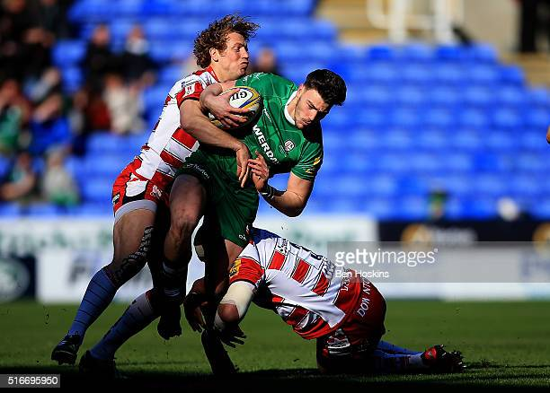 Johnny Williams of London Irish is tackled by Billy Twelvetrees and John Afoa of Gloucester during the Aviva Premiership match between London Irish...