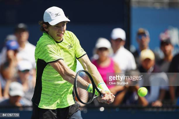 JohnPatrick Smith of Australia returns a shot against Jonathan Eysseric of France and Franko Skugor of Croatia during their first round Men's Doubles...